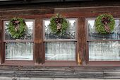 Trio of wreaths on old windows