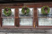 Trio of wreaths on old windows