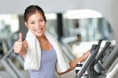 Happy fitness woman thumbs up in gym during exercise training on moonwalker treadmill.