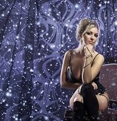 Young attractive woman in sexy lingerie posing over winter background