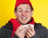 Ill young man with red nose, scarf and cap sneezing into handkerchief