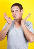 Surprised young man with hands in air, on yellow background