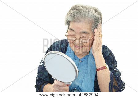 Picture or Photo of Old woman looking at herself in a hand mirror