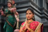 stock photo of hindu temple  - Beautiful young Indian woman in traditional sari dress praying in a hindu temple - JPG