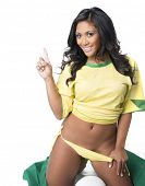 Beautiful young woman wearing Brazil national colors soccer team fan pointing.  Isolated against white.