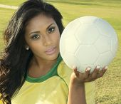 Attractive female soccer football player holding ball