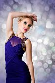 young beautiful woman with up style blond hair wearing tight blue evening dress with gold luxury des
