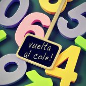sentence vuelta al cole, back to school in spanish, written in a blackboard label and a pile of numbers of different colors in the background