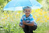 Rain and sunshine with a smiling boy holding an umbrella in a meadow of wildflowers