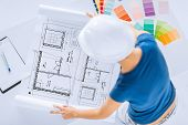 architecture, interior design and renovation concept -  woman in helmet working with color samples a