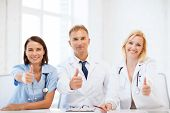 healthcare and medical concept - group of doctors on a meeting showing thumbs up