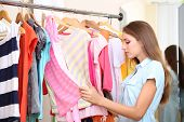 Beautiful girl chooses clothes on hangers on room background