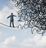 stock photo of overcoming obstacles  - Risk confusion business concept with a businessman on a high wire tight rope walking towards a tangled mess as a metaphor and symbol of overcoming adversity in strategy and finding solutions through skilled leadership facing difficult obstacles - JPG