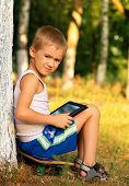 Boy Child Playing With Tablet Pc Sitting On Skateboard Outdoor With Forest On Background Game Depend