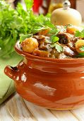 stock photo of stew pot  - Beef stew with vegetables and herbs in a clay pot  - JPG