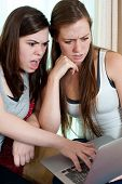 Two Girls Looking At A Lap Top.