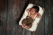 picture of sleeping  - Overhead shot of a 5 day old newborn baby boy wearing crocheted shorts and suspenders - JPG