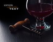 Glass Of Wine And A Corkscrew On A Black Table
