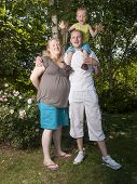 Happy Family With Pregnant Mother With Toddler In A Garden