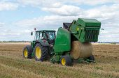 stock photo of hayfield  - A round baler discharges a fresh wheat bale during harvesting - JPG