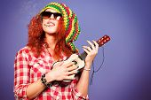 Portrait of a rastafarian girl playing her guitar.