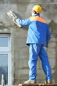 Male builder plastering exterior wall during industrial facade building with putty knife float