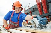 Male builder working with power tool circular saw machine cutting plastic parts at construction site