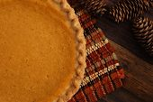 Freshly baked pumpkin pie with placemat and decorative pine cones on rustic wood background.