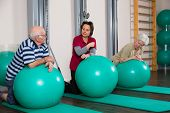 a physiotherapist explains two pensioners an exercise
