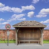 stock photo of bus-shelter  - An Old Wooden Bus Stop with Red Brick Wall and Blue Sky - JPG