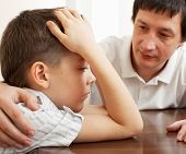 Father comforts a sad child. Problems in the family