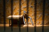 Conceptual Jail Photo With Iron Nail Sitting Behind Bars