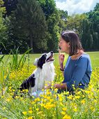 Young woman giving her border collie dog a reprimand in the park