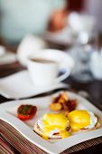 Delicious breakfast with eggs Benedict, vegetables and coffee