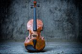 Cracked Violin on concrete wall background