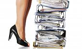 Businesswoman legs standing next to pile of ring binders. Stuck in work concept