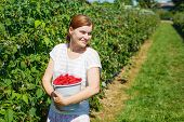 Young Woman Picking Raspberries On Pick A Berry Farm In Germany