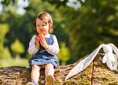 Little Baby Girl Eating Fresh Apple In Summer Park.