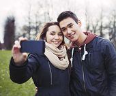 Cute Young Couple Taking Self Portrait In The Park