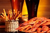 stock photo of crawdads  - Prepared crawfish and glasses of dark and light beer - JPG