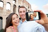 Happy travel couple taking selife by Coliseum, Rome, Italy. Smiling young romantic couple traveling