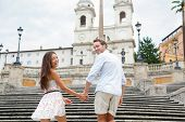 Couple holding hands on Spanish Steps, Rome, Italy. Happy romantic couple. Young interracial couple