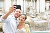 Tourist couple on travel taking selfie photo by Trevi Fountain in Rome, Italy. Happy young romantic