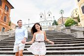 Happy romantic couple holding hands on Spanish Steps in Rome, Italy. Joyful young interracial couple