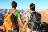 Couple holding hands looking at Grand Canyon. Romantic hikers enjoying view and romance while hiking