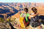 Hiking hikers in Grand Canyon enjoying view of nature landscape. Young couple relaxing during hike w