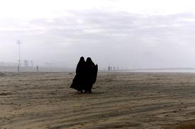image of yashmak  - Two Arabic women are in a yashmak go on the beach of the Atlantic ocean in Casablanca - JPG