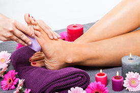 foto of pumice-stone  - Woman having a pedicure treatment at a spa or beauty salon with the pedicurist massaging the soles of her feet with a pumice stone to cleanse dead skin and stimulate the tissue - JPG