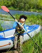 Happy young boy holding paddle near a kayak