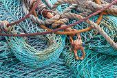 foto of coiled  - Abstract background with a pile of fishing nets ready to be cast overboard for a new days fishing - JPG